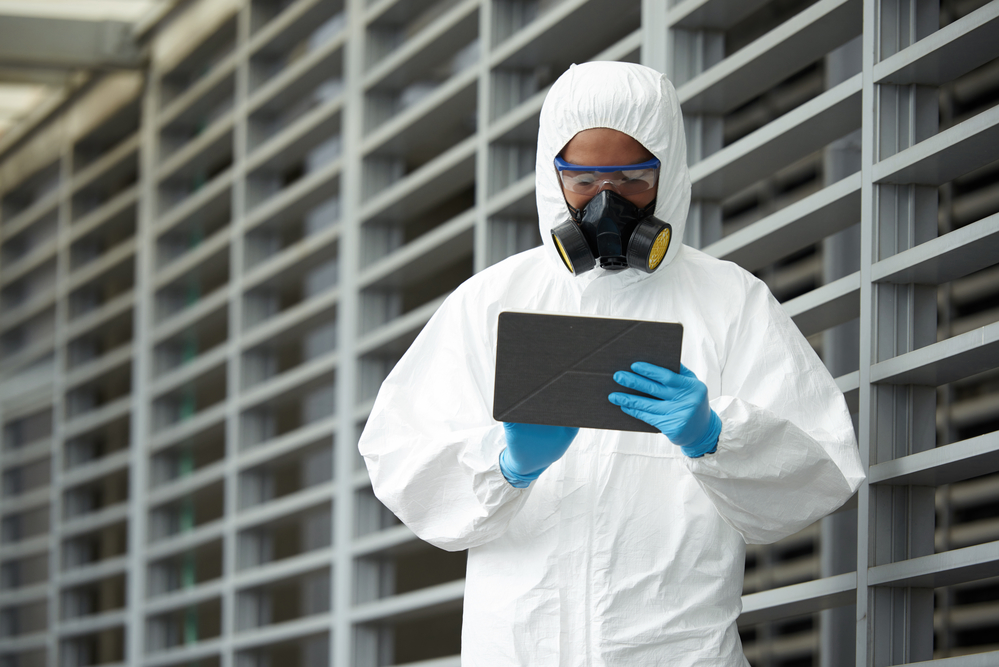 Scientist in chemical overall using digital tablet
